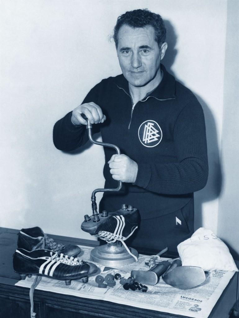 Adolf Dassler mentre sistema i tacchetti di un paio di scarpe da calcio