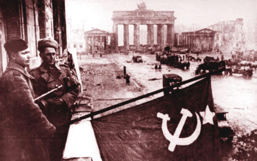 Militari russi espongono ad un balcone la bandiera sovietica. Sullo sfondo si può notare la Porta di Brandeburgo, simbolo della città di Berlino.