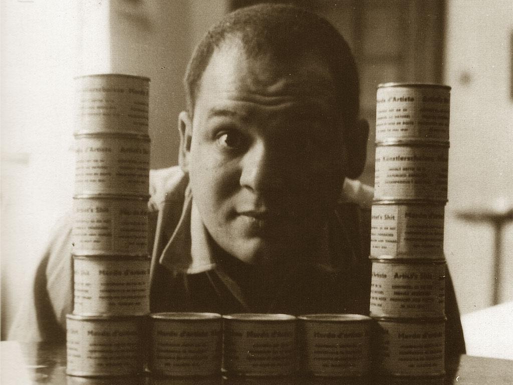 Una foto di Piero Manzoni con i suoi barattoli di Merda d'artista