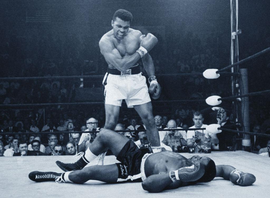 Cassius Clay (Muhammad Ali) in piedi e Sonny Liston al tappeto