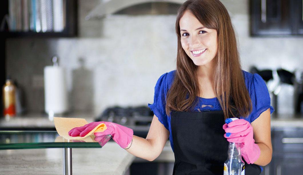 Una colf al lavoro mentre pulisce un ripiano della cucina