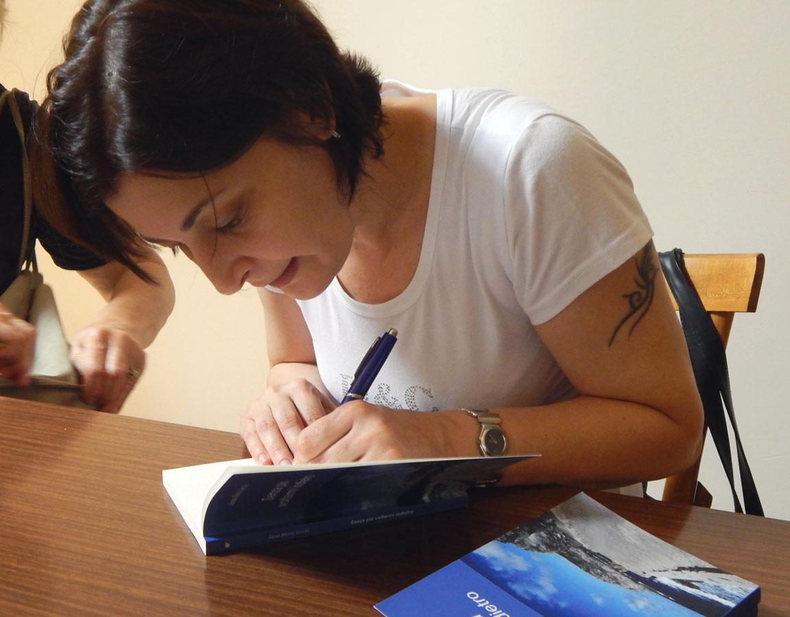 Anna Maria Secchi mentre firma una copia del suo libro
