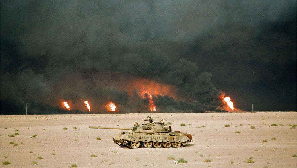 Guerra del Golfo: un carro armato statunitense con pozzi di petroli incendiati sullo sfondo