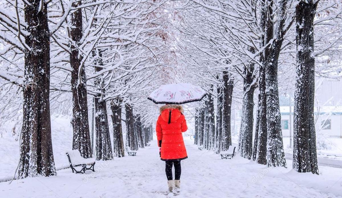 Neve: donna con cappotto rosso e ombrello nella neve