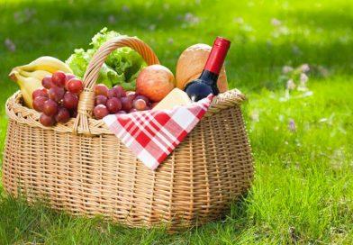 Un classico cesto da picnic con altrettanto classica tovaglia bianca e rossa