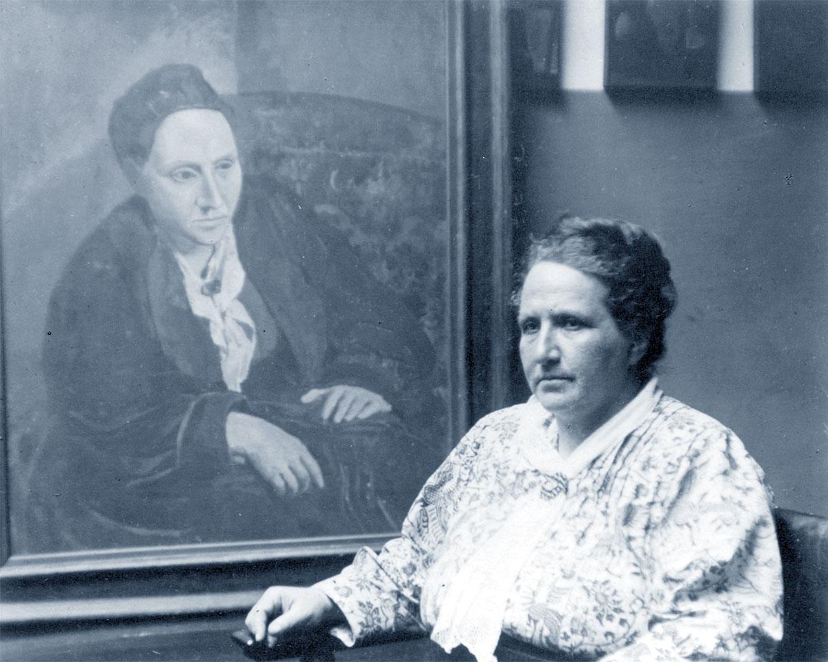 Gertrude Stein con alle spalle il ritratto realizzato da Picasso